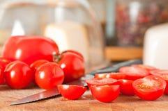 De rode rijpe tomaten van de besnoeiingskers op scherpe raad Royalty-vrije Stock Foto's