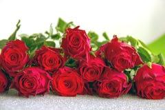 De rode rozen op zilveren achtergrond sluiten omhoog royalty-vrije stock fotografie
