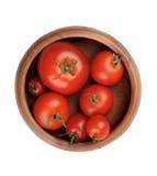 De rode sappige rijpe tomatenvruchten liggen in een houten kom Royalty-vrije Stock Afbeelding