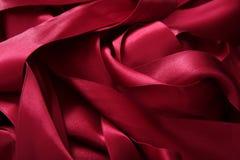 De rode satijnlinten in slordig knoeien textuur Royalty-vrije Stock Foto's