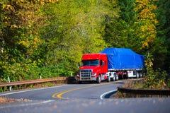 De rode semi aanhangwagen van het vrachtwagen vlakke bed bij het winden van de herfstweg stock fotografie