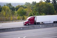 De rode semi adelborst van de vrachtwagenaanhangwagen op groene weg Royalty-vrije Stock Afbeeldingen