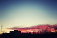 De rode silhouetten van de zonsonderganghemel van gebouwen Stock Foto