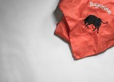 De rode sjaal met zwarte stier en de tekst Bayonne, symbool van Baskisch feria festival in Frankrijk, isoated op witte achtergron Stock Foto