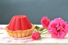 De rode, smakelijke cake met chocolade het vullen en nam struik op grijze achtergrond toe Stock Afbeeldingen