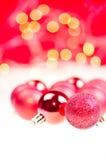 De rode snuisterijen van Kerstmis over rode achtergrond Royalty-vrije Stock Afbeelding