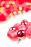 De rode snuisterijen van Kerstmis over wit en rood Stock Foto