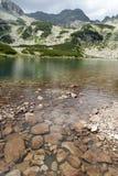 De rode stenen van het bergmeer met hoge pieken op de achtergrond Royalty-vrije Stock Foto's