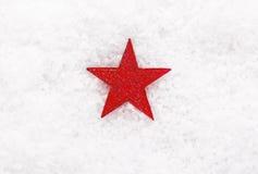De rode ster van Kerstmis op sneeuw Stock Afbeeldingen