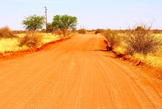 De rode stoffige woestijn van Kalahari van de zandweg, Namibië Royalty-vrije Stock Foto's