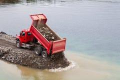 De rode stortplaatsvrachtwagen het leegmaken aarde vult royalty-vrije stock afbeeldingen