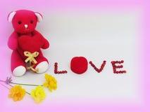 De rode teddybeer zit greep het rode hart met LIEFDE van letters voorzien gemaakt van rode zaden en rode doos van de ring met blo stock afbeeldingen