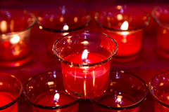 De rode theelichten in glaskruik verlicht het donkere omringen Stock Fotografie