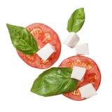 De rode tomaten, de mozarella en het basilicum isoalted Stock Fotografie
