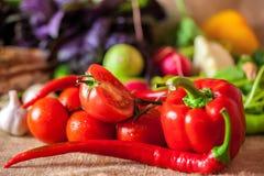 De rode tomaten en de rijpe Spaanse peper met water dalen, gezond voedselconcept royalty-vrije stock afbeeldingen