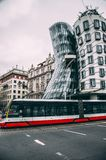 De rode tram die van Praag Dansend Huis overgaan Stock Fotografie
