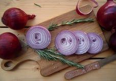 De rode ui hakte op een cuttering raad, twijgen van rozemarijn en korianderzaden Royalty-vrije Stock Foto