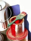 De rode verf kan met groen borstelen stock afbeelding
