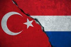 De rode vlag van Turkije op gebroken schadebakstenen muur en halve witte rode blauwe de kleurenvlag van Holland, de politiek van  stock illustratie