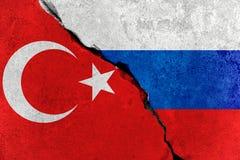 De rode vlag van Turkije op gebroken schademuur en half Russische witte rode blauwe kleurenvlag, verhoudingscrisis tussen Rusland stock foto's