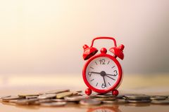 De rode wekker op stapel muntstukken in concept besparingen en geld het groeien of de energie spaart stock fotografie