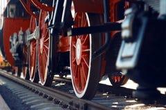 De rode wielen van een oude uitstekende stoomlocomotief stock afbeeldingen