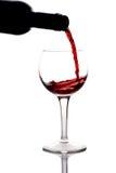 De rode wijn die pured in een wijnglas is Royalty-vrije Stock Afbeeldingen