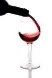 De rode wijn die pured in een wijnglas is Stock Afbeelding