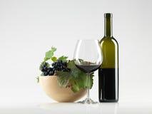De rode wijn van de fles, glas, druiven witte achtergrond stock fotografie