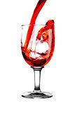 De rode wijn van de stroom in glas Stock Afbeeldingen