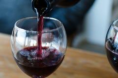 De rode wijn wordt gegoten in een glas - het concept dronkenschap en alcoholisme stock fotografie