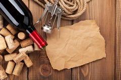 De rode wijnfles, kurkt en kurketrekker over houten lijst backgroun Royalty-vrije Stock Afbeelding