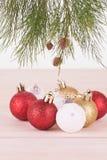 De rode, witte en gouden Kerstmissnuisterijen en tak van de pijnboomboom Stock Afbeeldingen