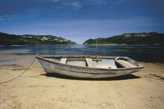 De roeiboot van de verlaging op strand Stock Afbeelding