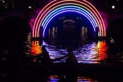 De roeiers gaan een kunstwerk in een kanaal op de het Waterkleuren van de bootroute tijdens het Lichte Festival 2016 van Amsterda Royalty-vrije Stock Foto's