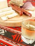 De Roemeense traditionele snack van de worsten van de kaasui paneert en pruimbrandewijn op een houten plaat Stock Foto