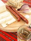 De Roemeense traditionele snack van de worsten van de kaasui paneert en pruimbrandewijn op een houten plaat Stock Fotografie