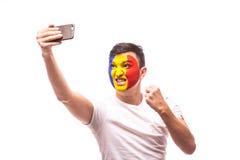 De Roemeense voetbalventilator neemt selfie foto met telefoon op witte achtergrond Stock Foto's