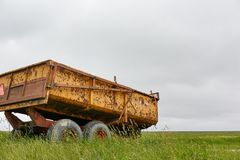 De roestige gele wagen van de landbouwbedrijftractor in groen landschap Stock Fotografie