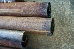 De roestige metaalpijpen van diverse diameters liggen op de concrete vloer Industriële Achtergrond stock foto