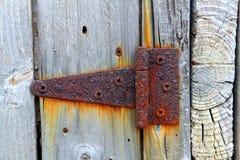 De roestige oude ijzerscharnier doorstond grijze houten deur Stock Foto