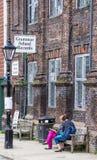 De ROGGE, het UK/eerste van JUNI 2014 - Twee onbekende vrouwen zit op een bank voor de winkel van Lage schoolverslagen Stock Afbeelding