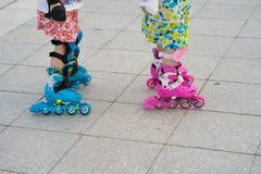 De rol van close-upkinderen het schaatsen Het leren openlucht te schaatsen Royalty-vrije Stock Foto's