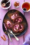 De rollade van het chocoladebiscuitgebak met bessenmousse op een plaat stock afbeeldingen