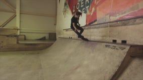 De rolschaatser in glazen maakt extreme stunt op springplank in skatepark uitdaging competition stock videobeelden