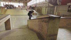De rolschaatser maakt extreme achtermisstap op springplank in skatepark Cameraman op rollen competition stock footage