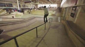 De rolschaatser maakt extreme misstap op lange omheining in skatepark springplank uitdaging competition stock video