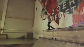 De rolschaatser maakt extreme misstap, sprong van springplank in skatepark uitdaging competition stock video