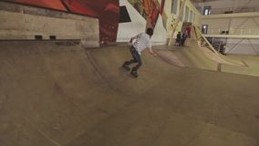 De rolschaatser maakt extreme stunt op omheining in skatepark springplank uitdaging competition stock videobeelden