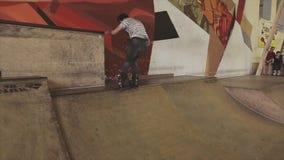 De rolschaatser maakt extreme stunt op springplank in skatepark Volledige ommekeer uitdaging competition stock footage
